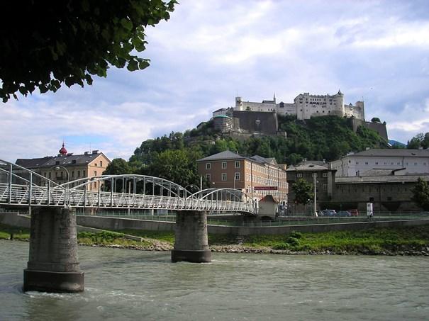 Puente sobre un río que lleva a un castillo, típico paisaje de la ciudad austriaca de Salzburgo.