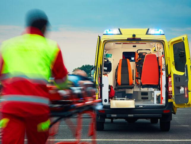 técnico de ambulancia llevando una camilla con un herido dentro de una ambulancia