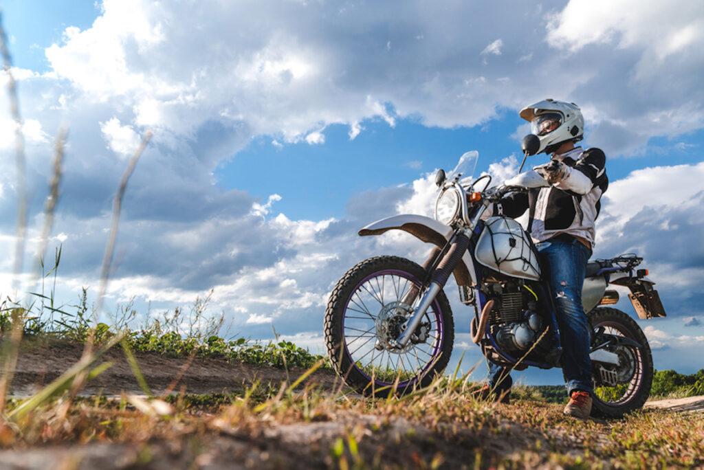 motorista subido en su moto por una linde