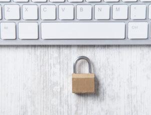 candado al lado del teclado de un ordenador portátil