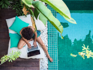 plano cenital de una mujer teletrabajando con su portátil desde una piscina