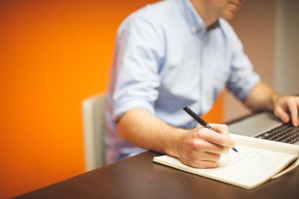 Un hombre escribe en un cuaderno, al lado de su ordenador.