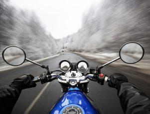 moto circulando por una carretera con paisajes nevados. El motorista lleva el equipamiento de invierno adecuado