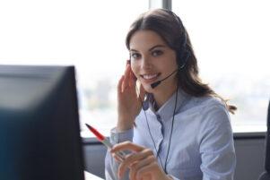 mujer joven atendiendo una llamada telefónica en su puesto de trabajo