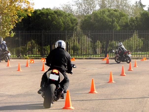 Pilotos sortean conos en una pista, durante un curso de conducción segura.
