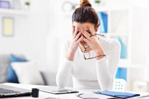 mujer apoyando los brazos y cabeza sobre el escritorio de su oficina