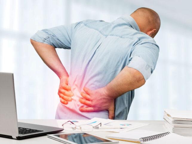 hombre en una oficina tocándose la parte lumbar de la espalda