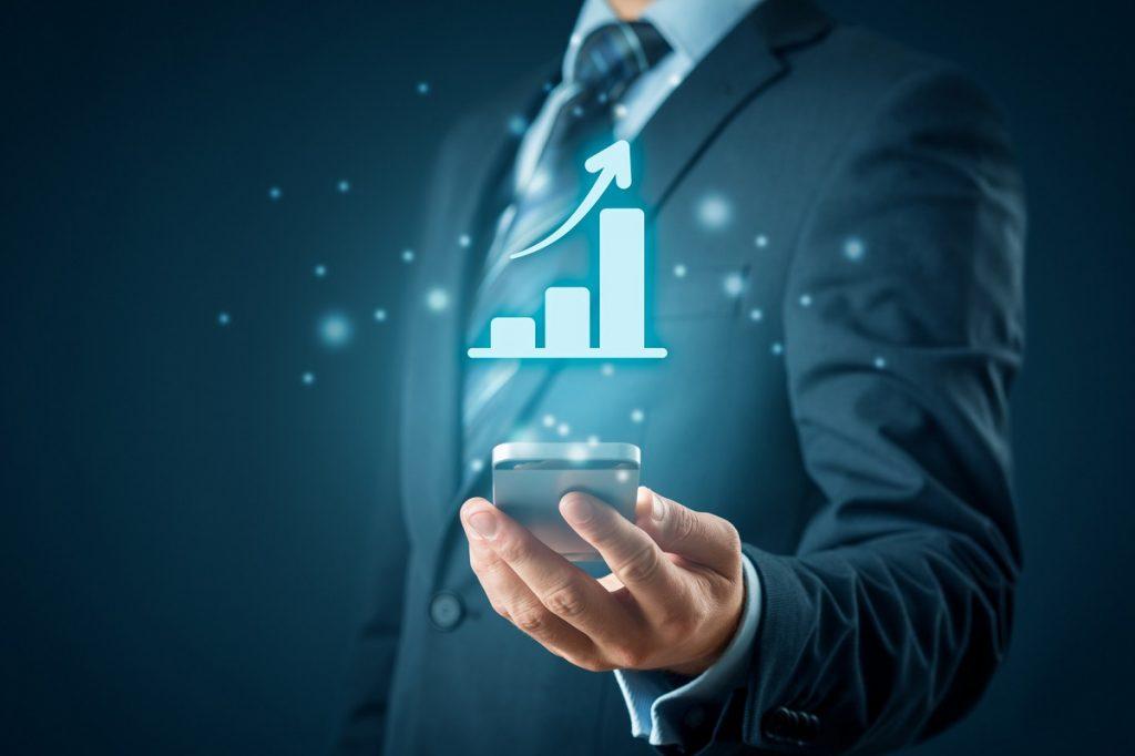 Hombre sostiene un móvil con la mano. Del móvil sale un gráfico que muestra crecimiento.