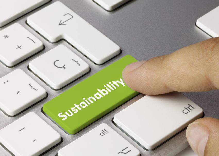 """vista en primer plano de un teclado de ordenador con teclas blancas y un botón verde con la palabra """"sostenibilidad"""" en inglés"""