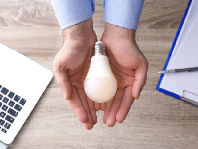 hombre sosteniendo una bombilla en sus manos sobre un fondo de un escritorio de una oficina