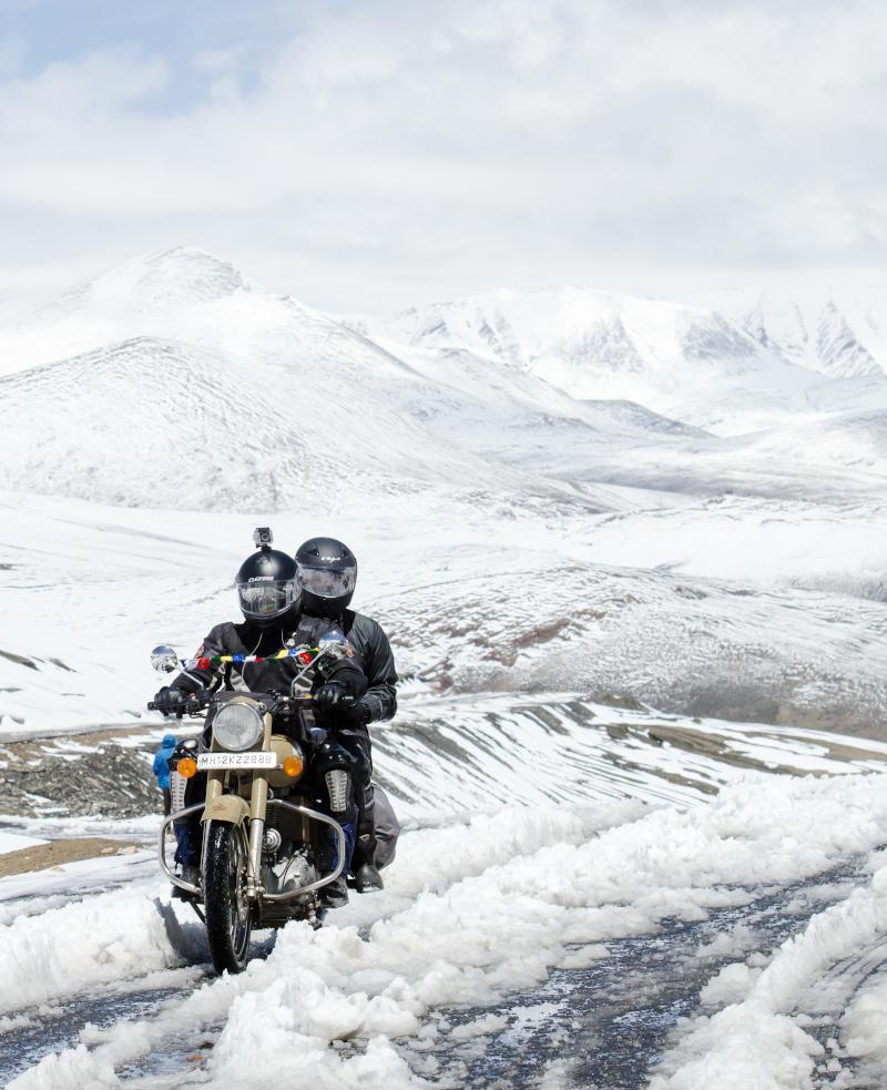 Una pareja recorre una ruta en moto por la nieve.